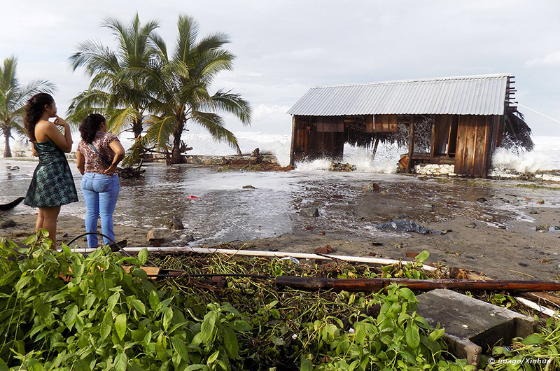People watch the strong waves caused by the hurricane Odile in the town of Tecpan de Galeana region
