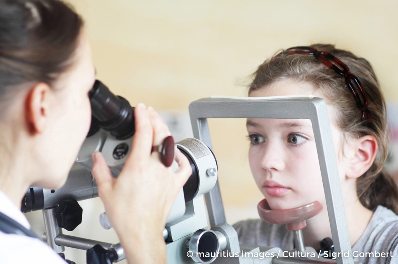 Optometrist examining girl's eyes