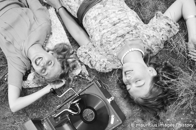 Zwei junge Frauen liegen im Gras und h??ren die neuesten Schlager vom Electrola Koffergrammophon, Deutschland 1930er Jahre. Two young women lying in a lawn and listening to the lastest hits from their Electrola gramophone, Germany 1930s.