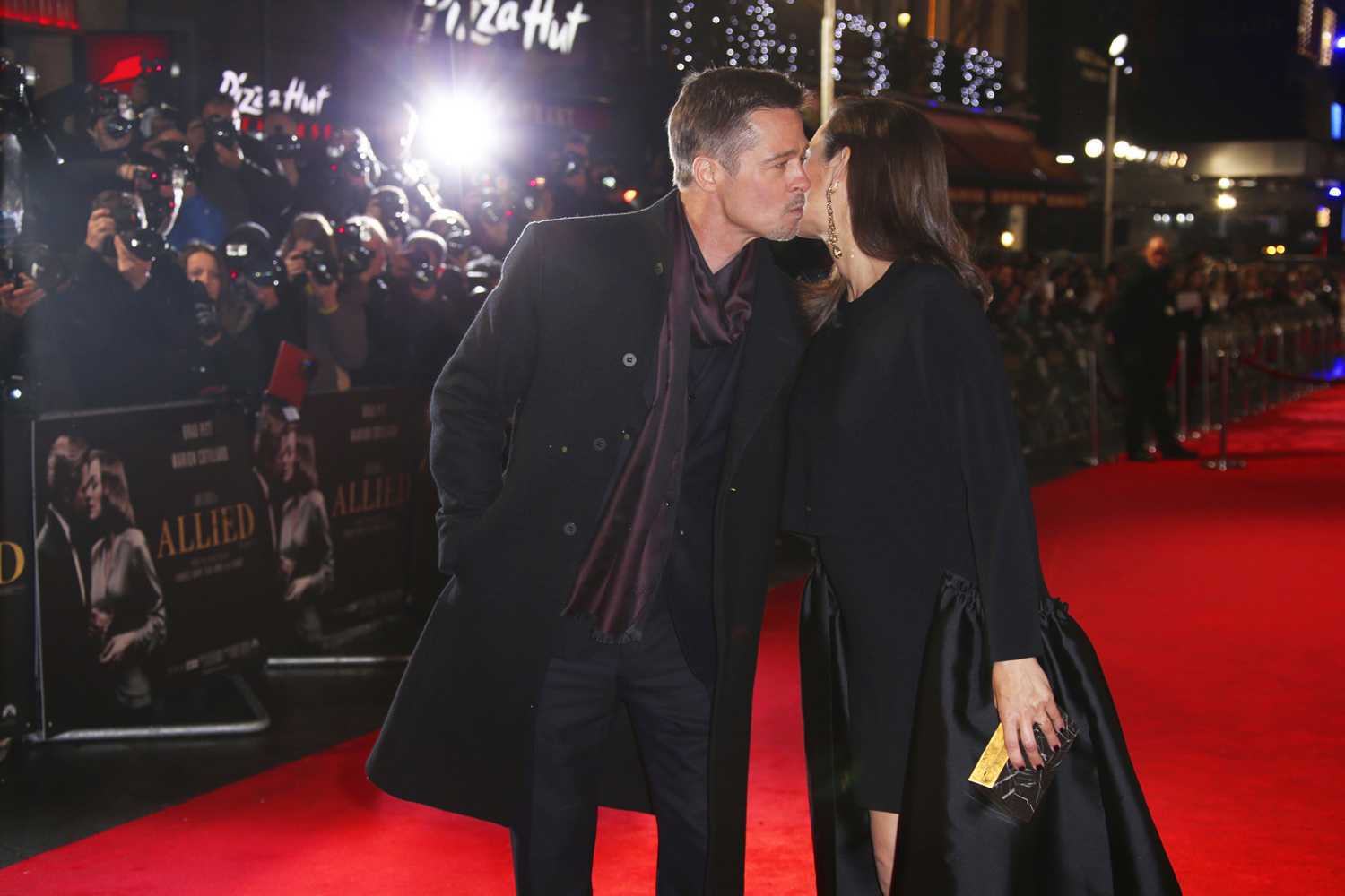Actor Brad Pitt greets fellow actor Marion Cotillard upon arrival at the premiere of the film 'Allied' in London, Monday, Nov. 21, 2016. (Photo by Joel Ryan/Invision/AP) |