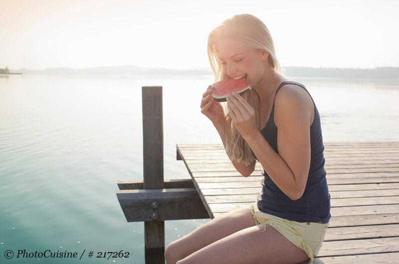 Jeune fille mordant une tranche de pastèque sur le ponton en bord de lac