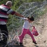 Flüchtlinge überwinden am 3. September 2015 einen Stacheldrahtzaun an der serbisch-ungarischen Grenze in Röszke. Die Flüchtlinge klettern über den inzwischen 175 Kilometer langen Zaun an der Grenze zwischen Serbien und Ungarn.