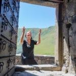 Georgien, Tsminda Sameba, Eingangstür, Blick aus dem Kloster auf diese betende Frau