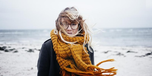 Portrait of young woman with tousled hair at beach