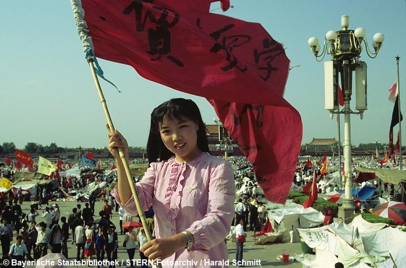 """Das Gesicht der Revolte. Furchtlos und zuversichtlich schwenkt die 20jährige Biologiestudentin Xia die Fahne ihrer Hochschule über dem """"Platz des Himmlischen Friedens""""; auf dem die Demonstranten ihr Lager aufgeschlagen haben. Sie kämpft nicht gegen den Sozialismus; aber gegen Unfreiheit. Dia: 56/05 *** Local Caption *** Scan ist im Original als Dia vorhanden!!!!"""