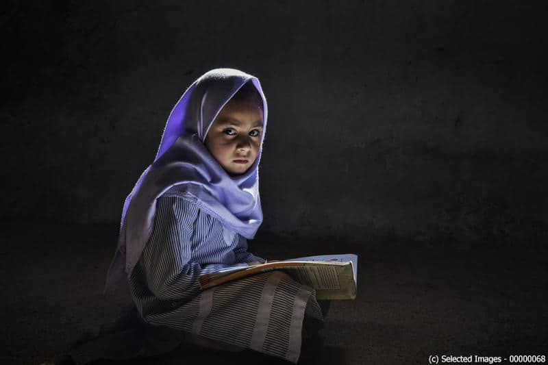 Abieeha, a 7 year old young girl, sits on the floor with a book in her lap, at Al-Hadi Kids Academy, in the village of Akber Abad, northern Pakistan on October 15, 2017. (Photo by Andrea Francolini/Selected Images)  SELECTED IMAGES EXCLUSIVE; TEXT AVAILABLE at media ID: 00028569