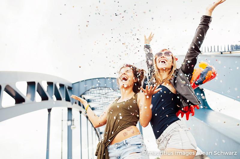 zwei junge Frauen werfen Konfetti in die Luft und freuen sich