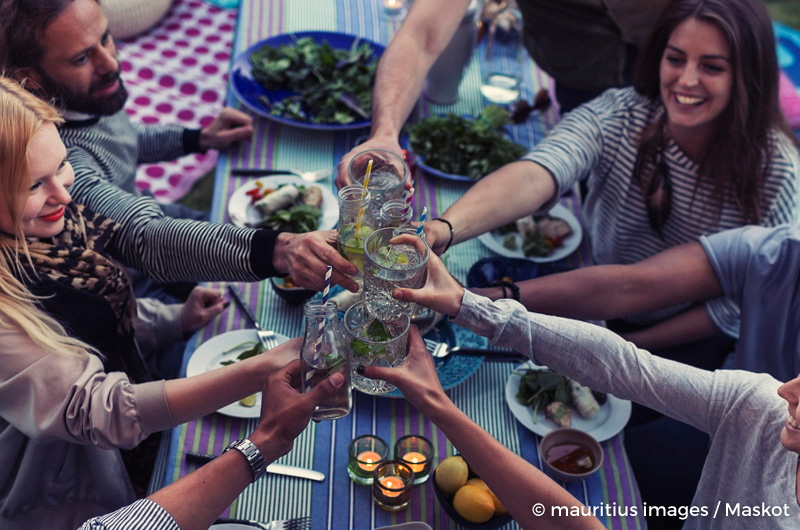 High angle view of multi-ethnic friends toasting drinks at dinner table in yard