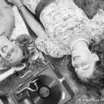 Zwei junge Frauen liegen im Gras und h??ren die neuesten Schlager vom Electrola Koffergrammophon, Deutschland 1930er Jahre. Two young women lying in a lawn and listening to the lastest hits from their Electrola gramophone, Germany 1930s.